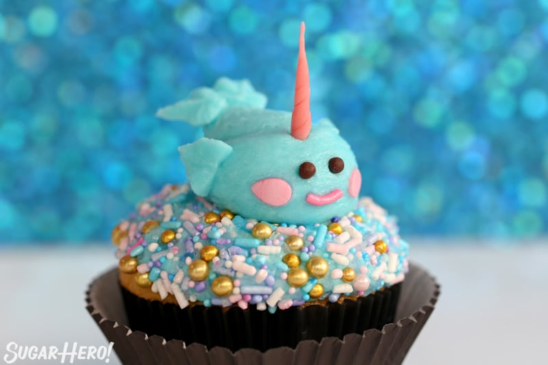 Close-up of a cupcake topped with sprinkles and a buttercream narwhal