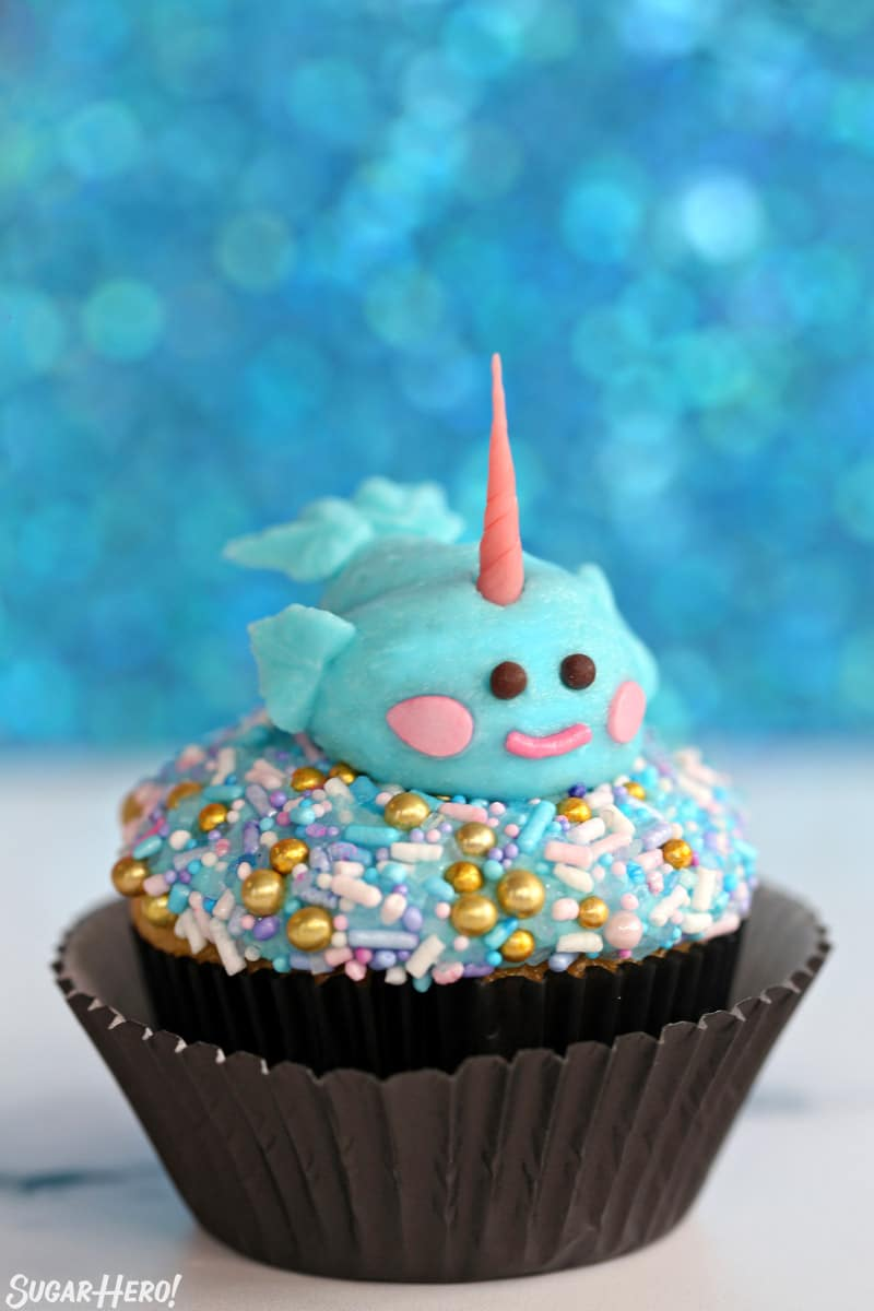 Single cupcake topped with a sprinkle mix and a buttercream narwhal