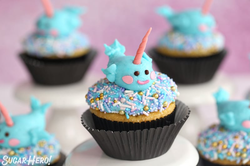 A group of cupcakes topped with sprinkles and piped buttercream narwhals