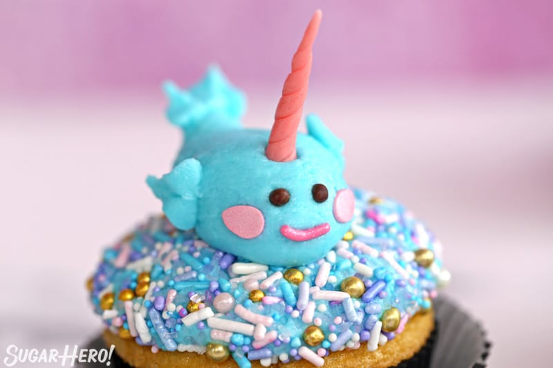 Sprinkle-topped cupcake with a buttercream narwhal on top