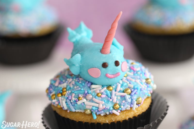Group of cupcakes with sprinkles on top and a cute buttercream narwhal