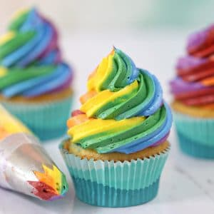 Three cupcakes with colorful rainbow icing and a piping bag next to it