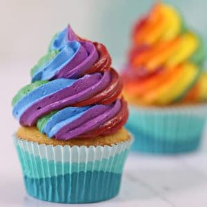 Two cupcakes with big swirls of rainbow frosting