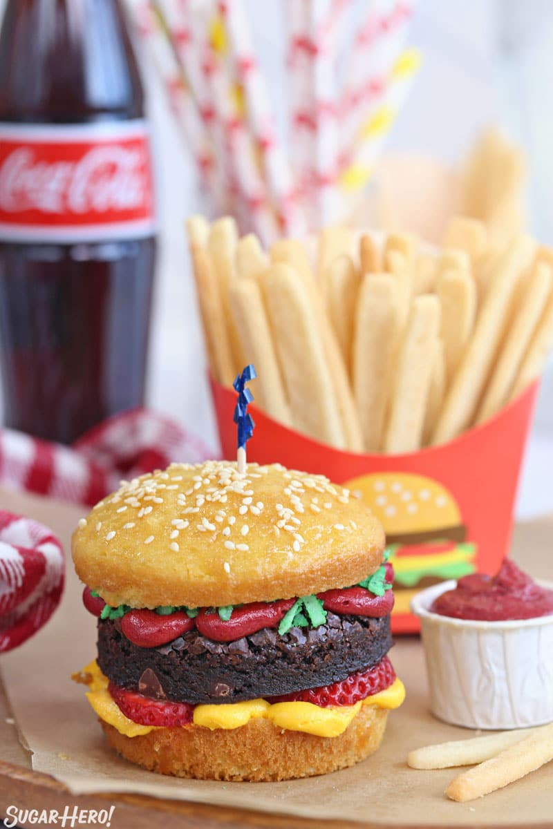 A hamburger cupcake with sugar cookie french fries and a bottle of Coke