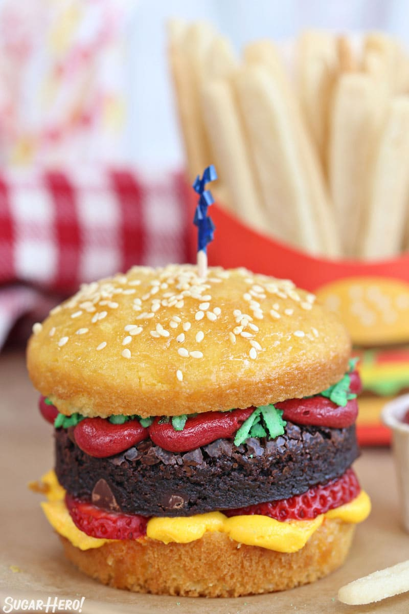 Yellow cupcake decorated to look like a hamburger, with sugar cookie french fries in the background