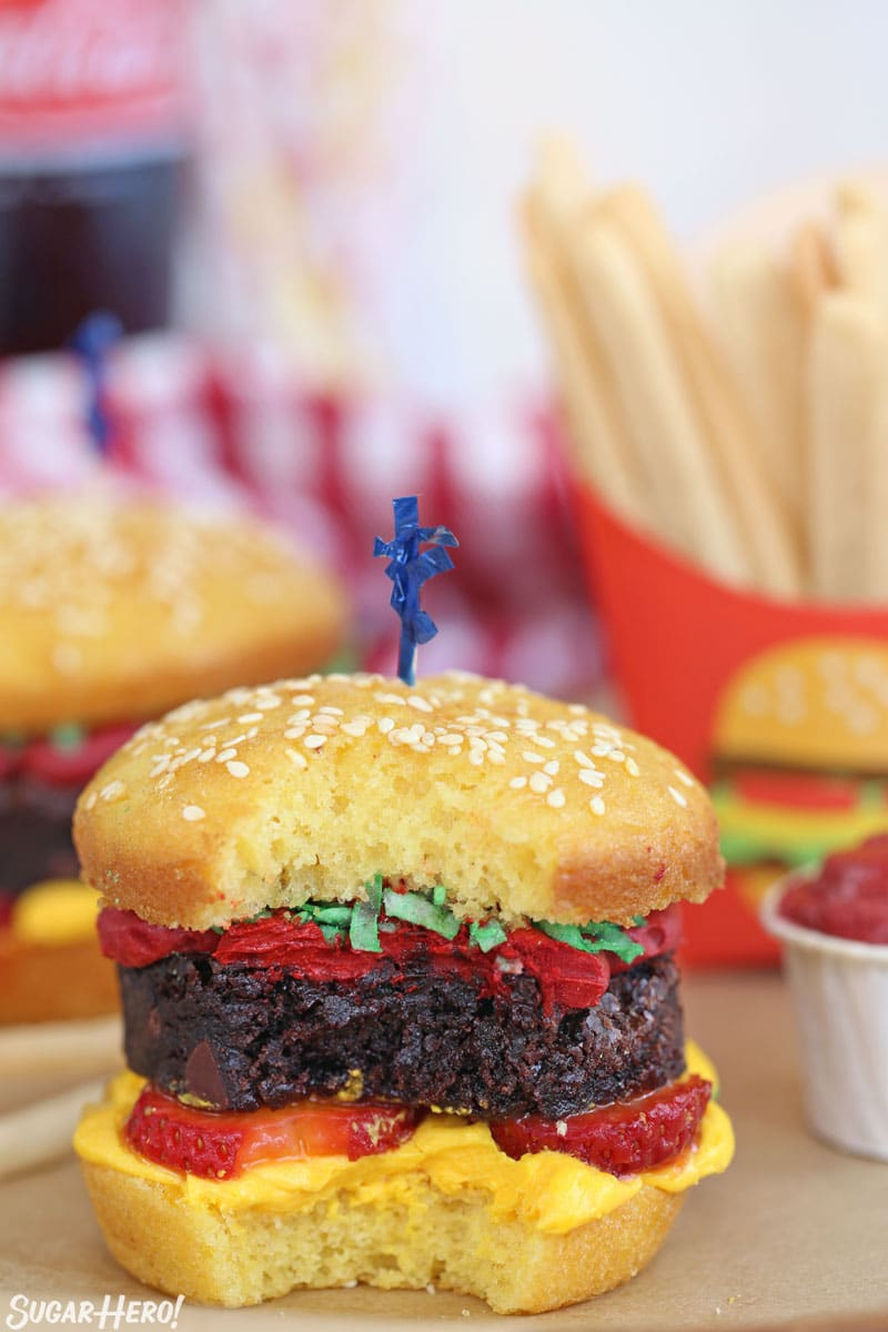 A hamburger cupcake with a bite taken out of it.