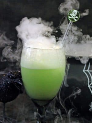Halloween punch bubbling in a green glass goblet.