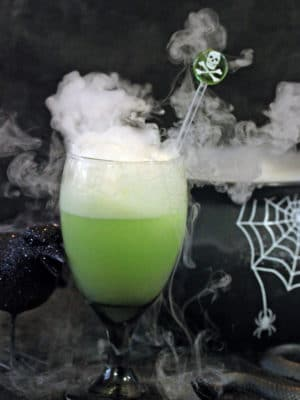 Goblet of green punch with smoke coming out the top and a black cauldron in the background