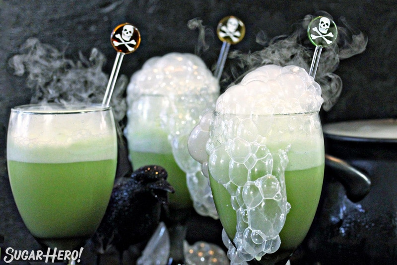 Close-up of three goblets with green punch and smoke bubbling out the top