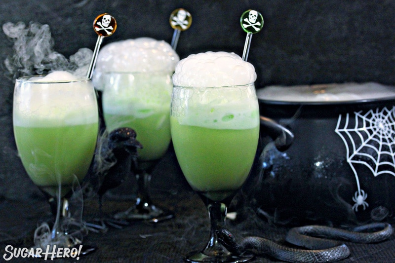 Three goblets of green punch with skull and bones swizzle sticks