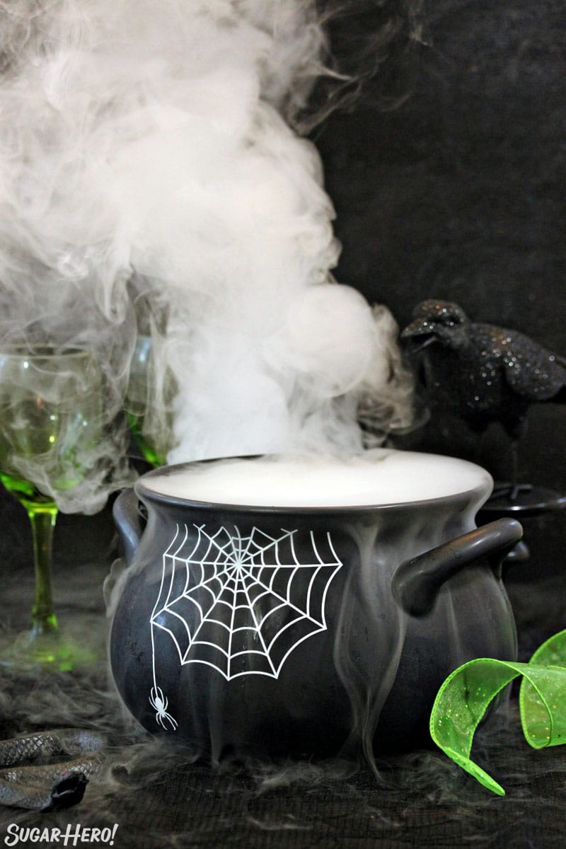 Black cauldron with a spiderweb pattern and smoke coming out the top