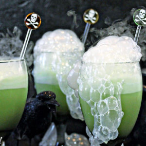 Three goblets of green punch with smoke coming out and a skull and bones swizzle stick