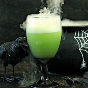 Goblet of green punch with smoke coming from the top and a black raven next to it