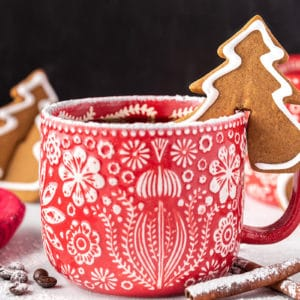 Tree-shaped Gingerbread Cookie Mug Topper on the rim of a red and white mug