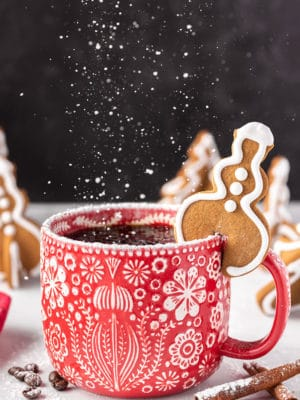 Snowman-shaped Gingerbread Cookie Mug Topper on a red mug with powdered sugar raining down