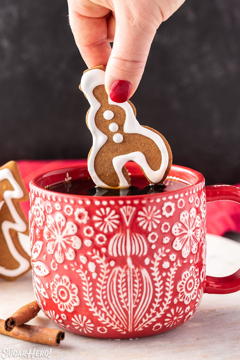 Hand dipping a snowman-shaped Gingerbread Cookie Mug Topper into coffee