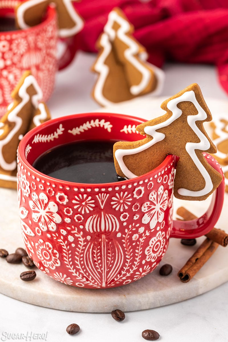 Tree-shaped Gingerbread Cookie Mug Topper on the edge of a red and white mug
