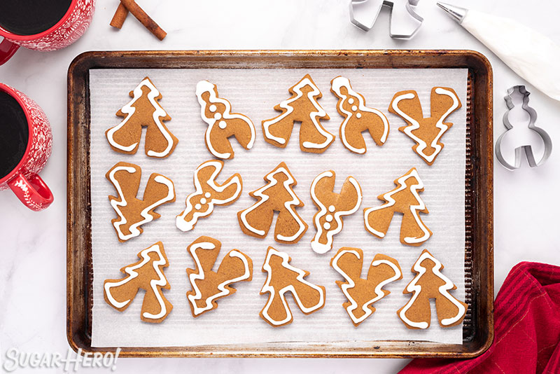 Baking sheet with baked and frosted Gingerbread Cookie Mug Toppers on parchment