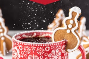 Snowman-shaped Gingerbread Cookie Mug Topper with powdered sugar with overlay text for Pinterest