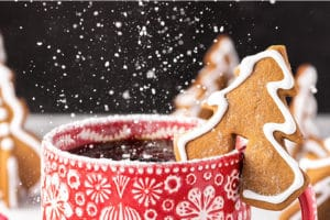 Tree-shaped Gingerbread Cookie Mug Topper with powdered sugar being sprinkled on with overlay text for Pinterest