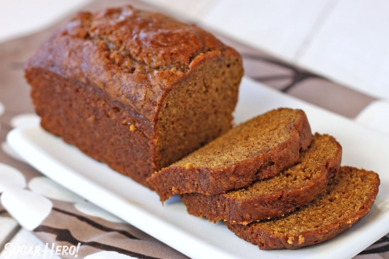 Loaf of pumpkin bread on white plate with several slices in front