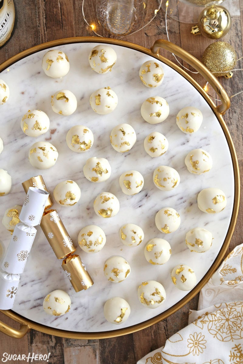 Overhead shot of Champagne White Chocolate Truffles on a white marble tray with party poppers