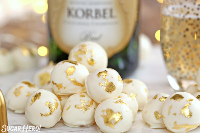 Champagne White Chocolate Truffles with gold leaf decorations, in front of a bottle of champagne