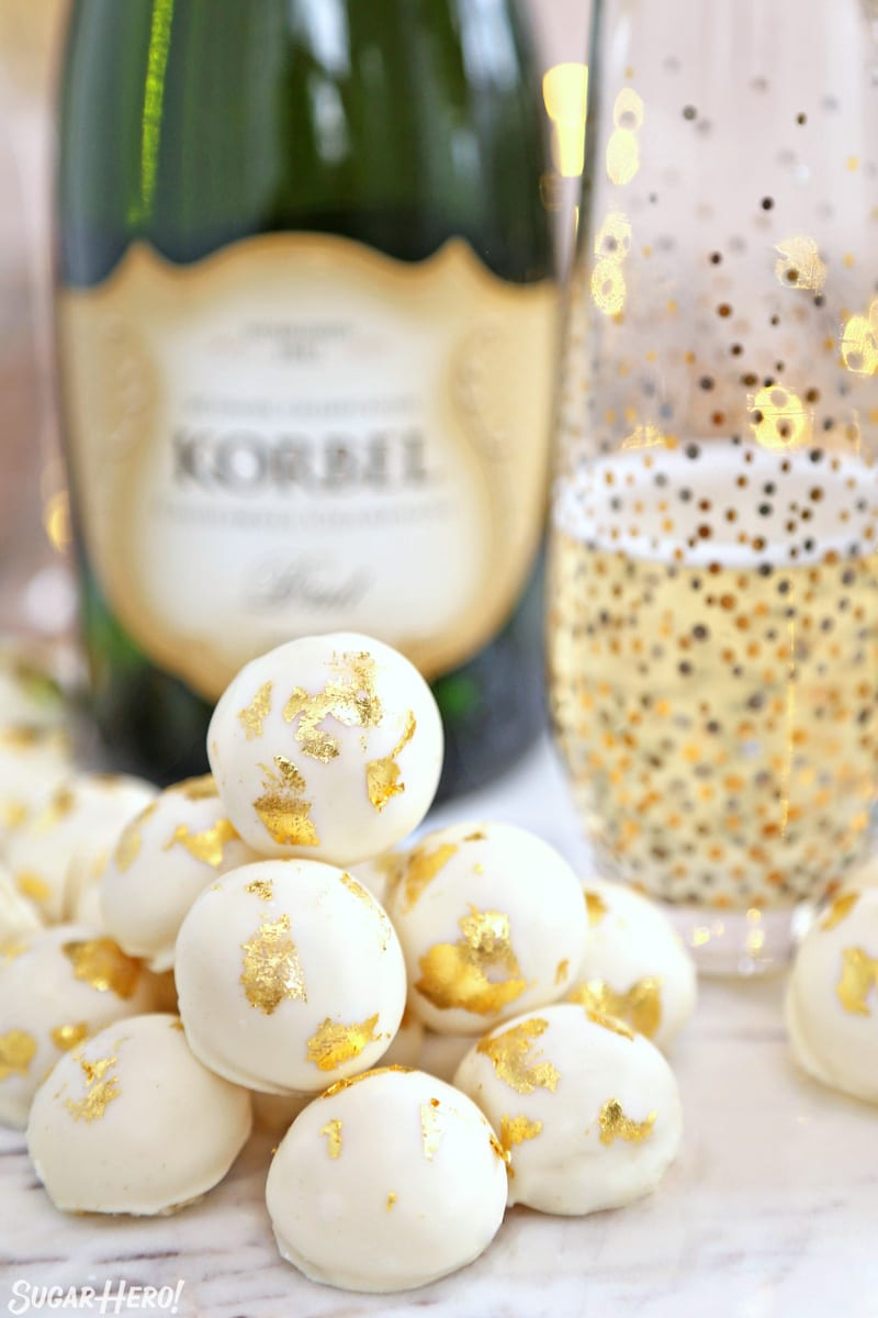 Champagne White Chocolate Truffles in a pile in front of a bottle of champagne