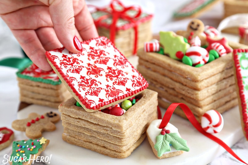 Hand placing and red and white decorated cookie lid on an Edible Christmas Cookie Box