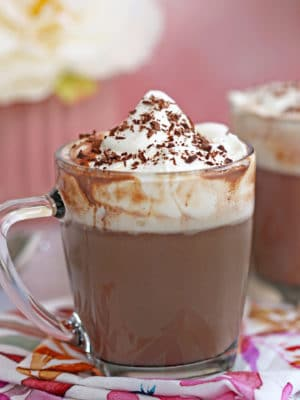 Mug of slow cooker hot chocolate with whipped cream and chocolate shavings on top