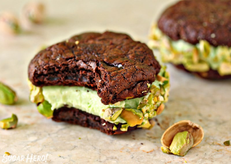 Chocolate Pistachio Sandwich Cookie on a marble board with a bite taken out of it