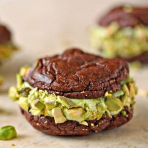 Chocolate Pistachio Sandwich Cookie on a marble board with pistachios scattered around