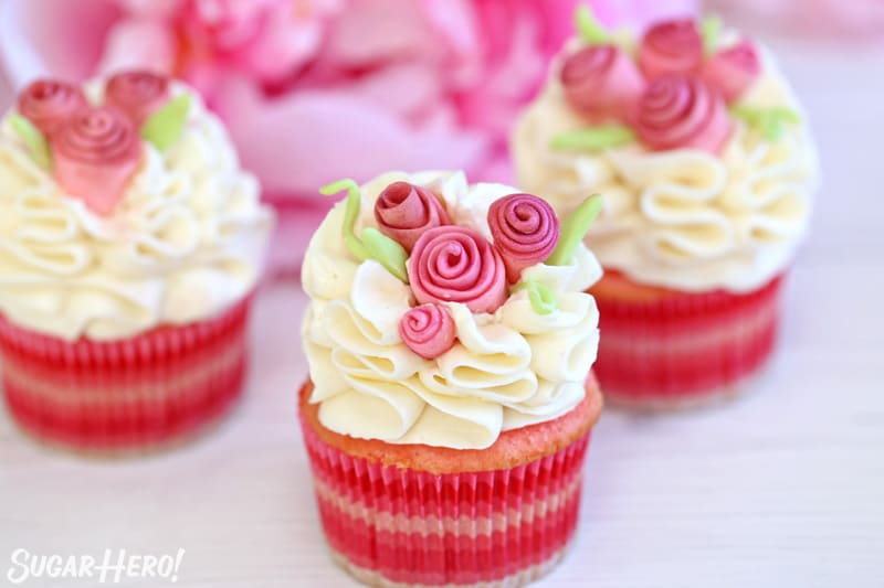 Group of pink cupcakes with ruffled white frosting and fondant flowers