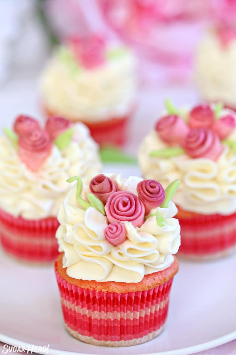 Group of pink cupcakes with white frosting and pink fondant flowers