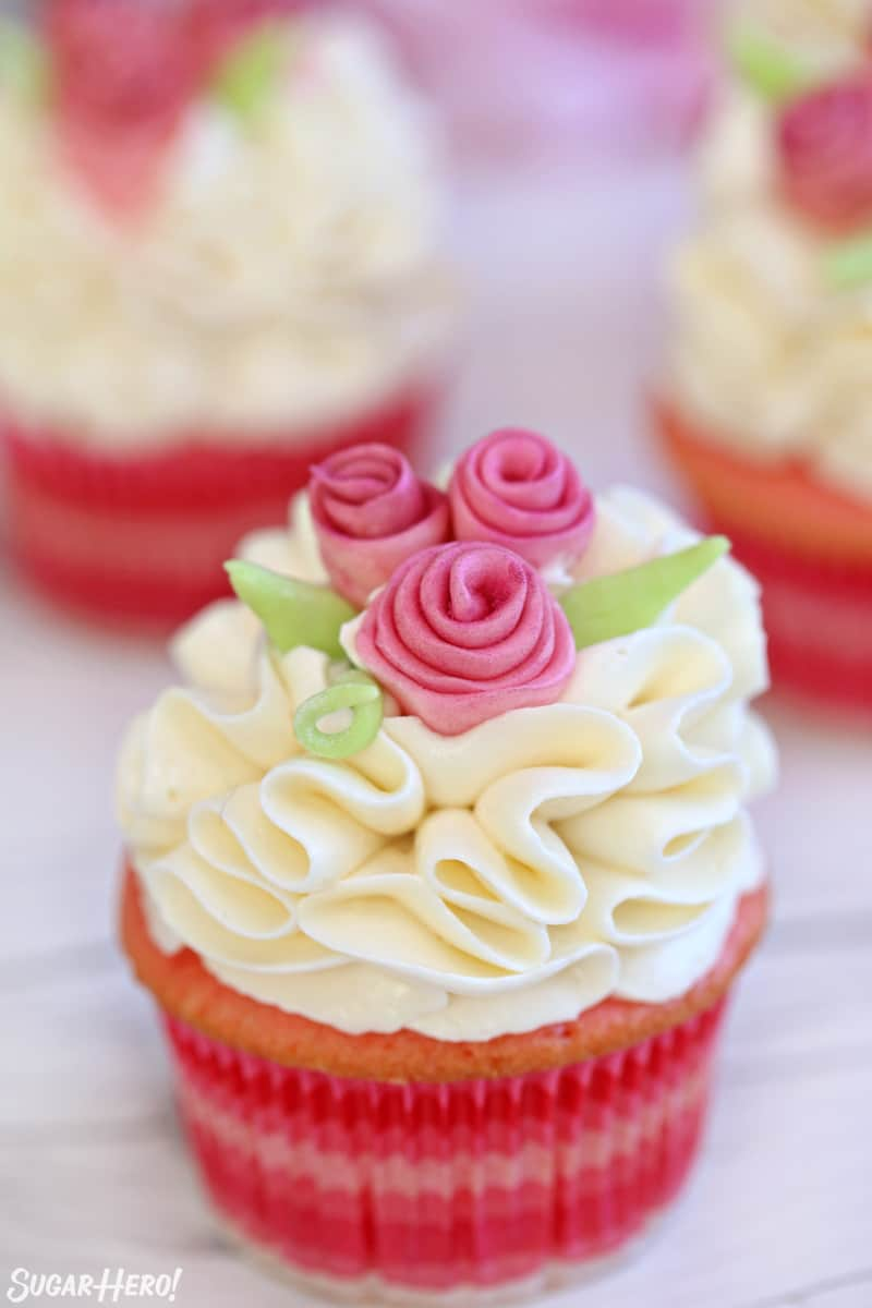 Pink cupcake with white ruffled frosting and pink fondant flowers