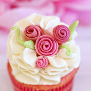 Close up of cupcake with white ruffled frosting and pink fondant flowers