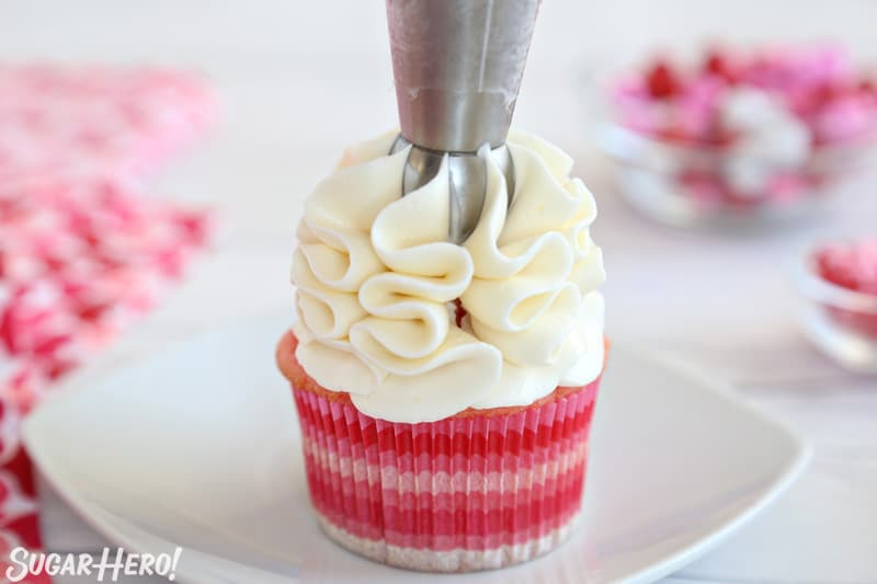 Piping white buttercream ribbons onto a pink cupcake