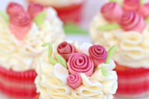 Photo of frosted cupcake with fondant flowers and text overlay for Pinterest