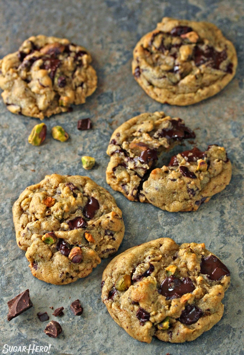 Five Pistachio Chocolate Chunk Cookies on a blue tile