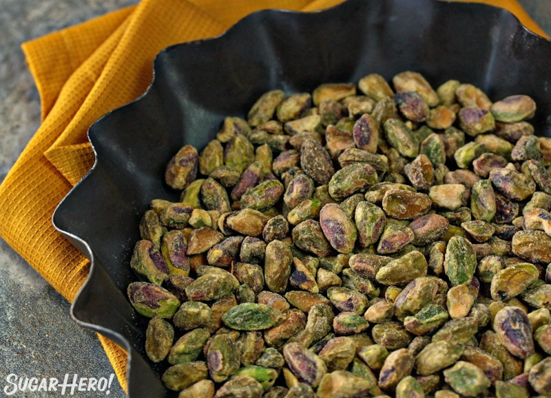 Fluted metal dish filled with shelled pistachios