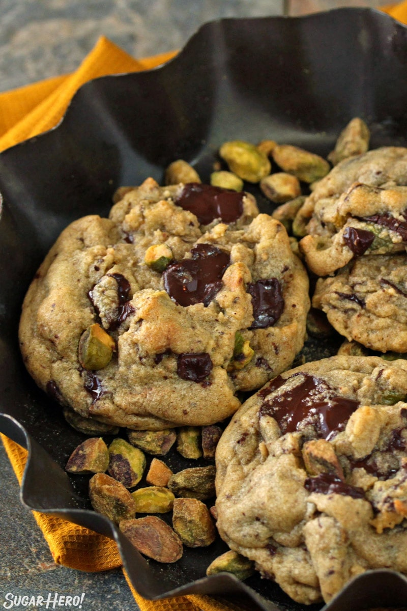 Pistachio Chocolate Chunk Cookies in a fluted dish of pistachios