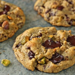 Close-up of Pistachio Chocolate Chunk Cookies on a blue tile board
