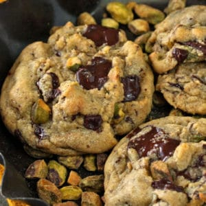 Close-up of Pistachio Chocolate Chunk Cookies in a dish of pistachios