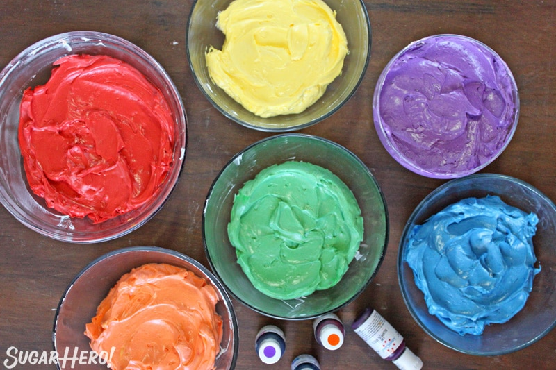 Overhead shot of 6 bowls of Colorful Rainbow Frosting grouped on a brown background