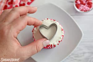 Placing a small heart-shaped cookie cutter on top of a cupcake