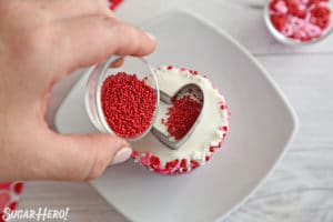 Filling the inside of a cookie cutter with small round sprinkles