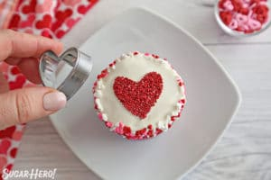 Removing a cookie cutter from the top of a frosted cupcake