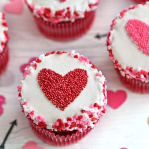 Close-up of a cupcake with a red heart-shaped sprinkle shape in the center