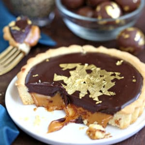 Baileys Chocolate Caramel Tart on a white plate with caramel dripping out