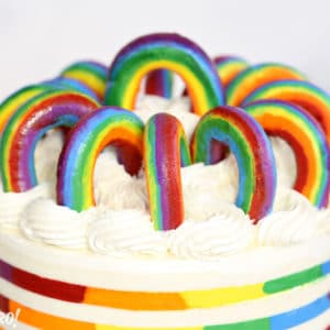 Buttercream Rainbows in a circle on top of a rainbow striped cake